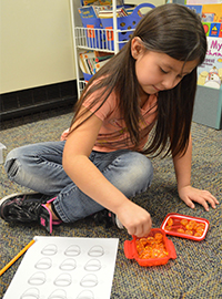 First-grade student Alexa Mejia counts with shiny counters