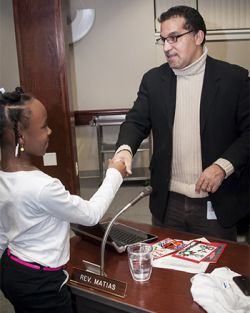 John Matias connects with a student at a school board meeting
