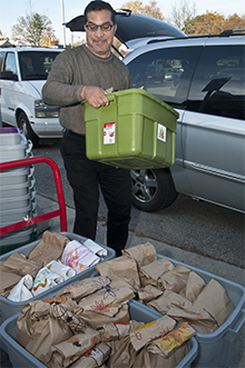 John Matias loads up supplies and food that will be distributed to students who need them