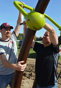 Trevor Brown, left, a Cedar Trails parent, and Steve Harper, husband of Co-principal Jennifer Harper, install a slide