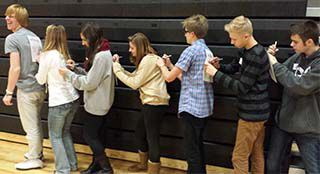 Rockford High School junior Christian Walters, left, heads a line of students signing pledges to have each other's backs