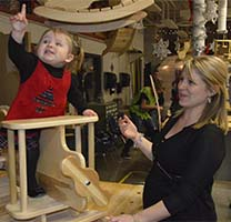 Anne Albert, 17 months, tries out one of the rocking airplanes helped by her mother, Kate