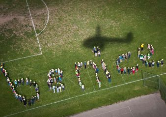 A shadow of the helicopter is cast above Grand Rapids Public Schools Riverside Middle School students' be nice formation