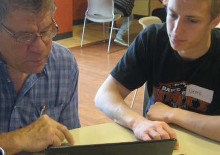 Byron Township resident Marv Feyen learns to use his laptop with Byron Center senior Derek Grit.