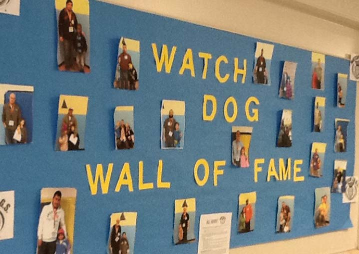 After spending the day at school, Watch DOGS volunteers get a photo in the Hall of Fame, one of students' favorite perks, says teacher Haley Bumgart