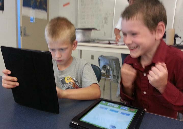 Kent City Elementary School third-grade Jordan Senkowski and Connor Flegel play reading games on iPads during Reading Rocks! summer program
