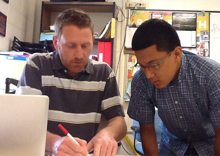 Joe Lober, part of the intervention team, helps Eduardo Ramirez solve some problems before he retakes a unit test