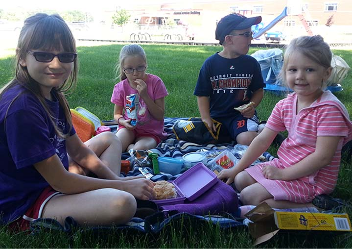 Kent City Elementary students Gabby Chrapek, Alyssa Sindecuse, Jack Jeffreys and Hayla Goble eat lunch outside during during Summer Fun Camp