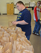 Andy Glerum, a Region One Transition Services student from Cedar Springs, helps sort lunch bags to be sent home with students