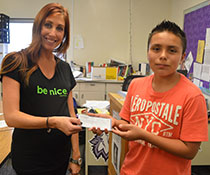 Kandice Sloop, education coordinator for Mental Health Foundation of West Michigan, receives a $200 donation after Giovanni Diaz's speech on the Be Nice Campaign received the most votes in his class