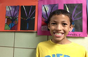 Godfrey Lee Elementary fifth-grader Jayden Miller, shown with a piece of his artwork, was one of two students in the district whose work was selected to be part of the Language Artists exhibition at the GRAM