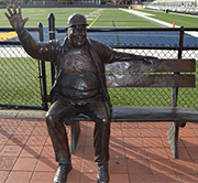 A bronze statue of Jimmy Gerken welcomes all to the football field