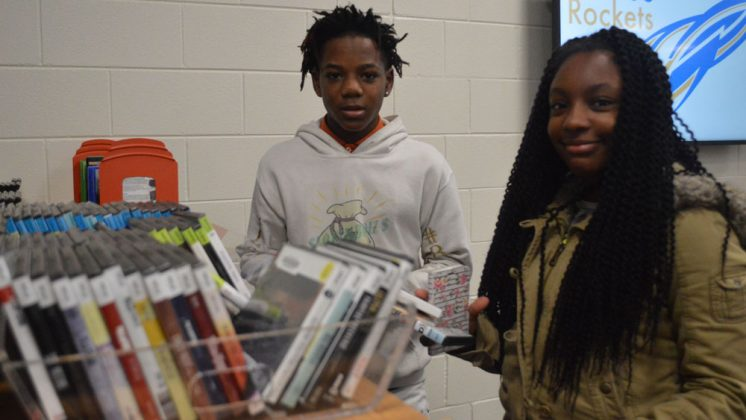 Kelloggsville ninth-grader Ta'mya Bell and seventh-grader Micah Atkins check out movies at the new library inside the high school