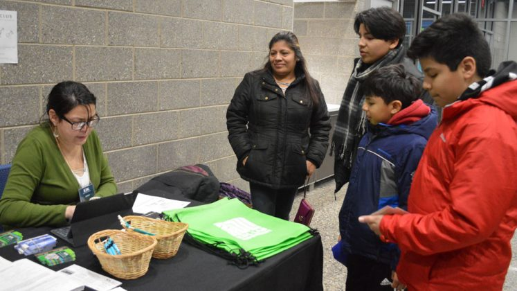From left, Maria Vicario, eighth-grader Pablo, sixth-grader Samuel and third-grader Angel sign up for library cards with help from a KDL staff member