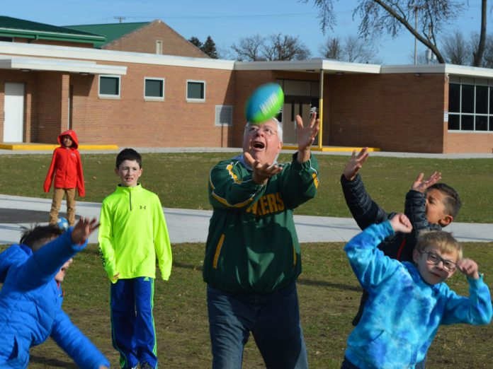 "Volunteer grandparent Ernie Sandona, affectionately called ""Papa Belly Floppa,"" shows his football prowess at Central Elementary School recess"