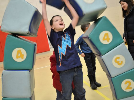 First-grader Jayden Pelletier crashes through an (obviously interactive) archway exhibit
