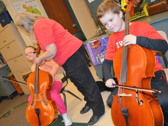 Nevaeh Orear, left, and Aden Cole try the cello with help from Lorene Turkalo, cellist with the Grand Rapids Symphony