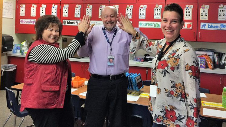 First-grade teachers Marcia Powell (left) and Megan Taylor have come to depend on Dale Allers, a 10-year classroom volunteer