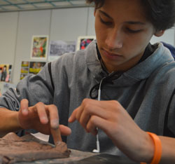A student of art teacher Derek Johnson uses his finger to smooth out clay after adding pieces