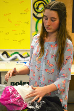 Evangelynn Detmer smooths plaster on classmate Alivia Beckett's face