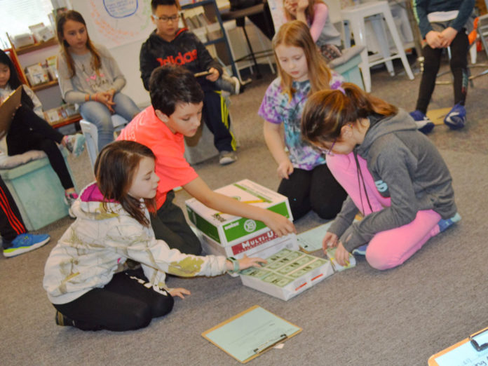 "Bridget Bennett's fourth-graders use the ""fishbowl"" style of problem-solving to figure out how to fit a million dollar bills into a box. Students are from left: Aubrey Sieler, Sam Bauchan, Fiona Overdevest and Mady Scarlato"