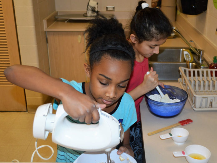 Tamyah Yarbrough, left, and Evelyn Reyes mix up a batch of best-selling oatmeal cookies