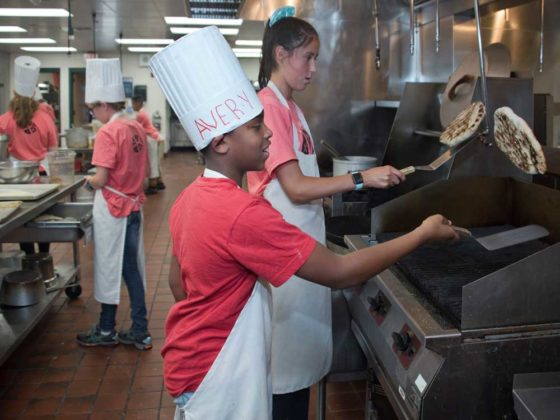 Avery Jones, seventh grade, Crestwood Middle; and Vivien Enrico, eighth grade, Forest HIlls Northern Middle; learn how to make, grill and flip pizza crust on a hot grill