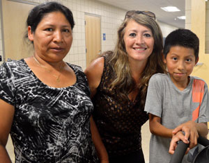 Kindergarten teacher Patricia Zellers, center, greeted fifth-grader Danny Perez and his mother, Floricelda