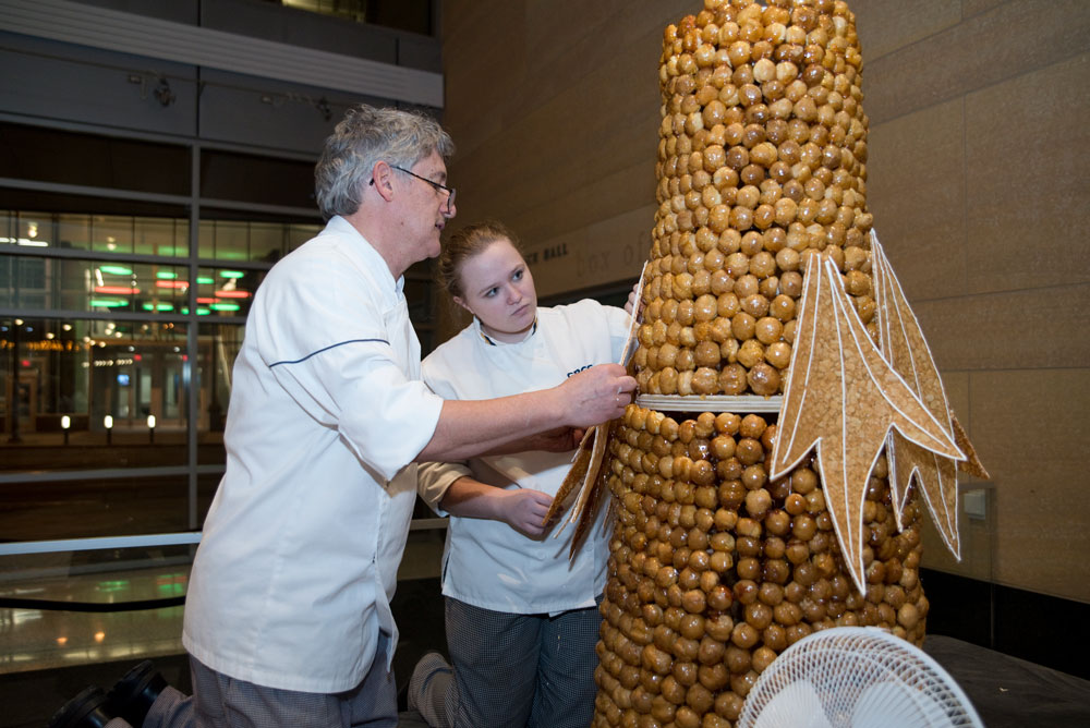 Professor Gilles Renusson, a certified master pastry chef and renowned sugar artist, attaches a branch to the croquembouche, made of 1400 shous (unfilled cream puffs). Student Isabella Patterson assists. It took 24 lbs of caramel to glue together