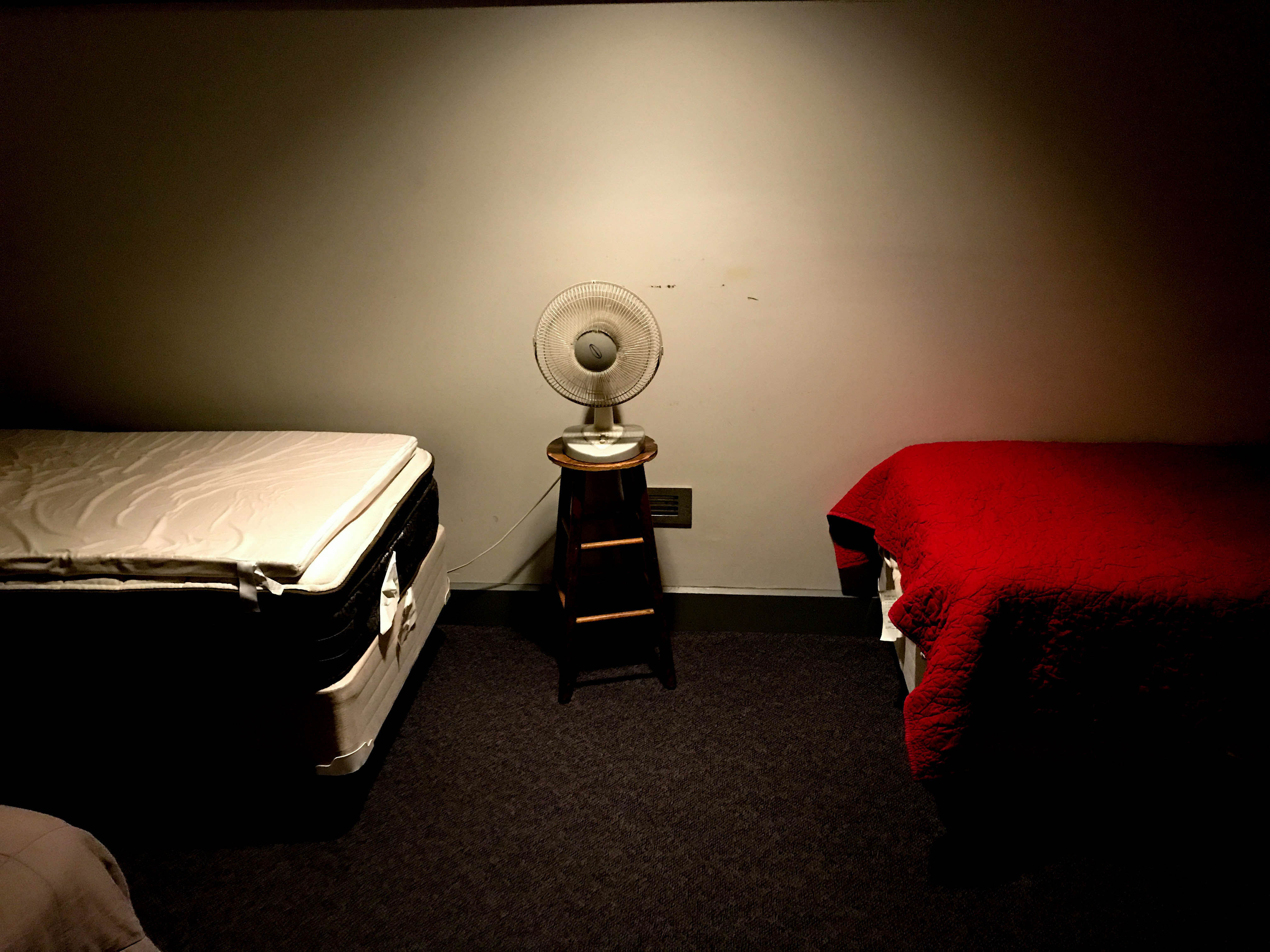 Two beds in the firefighters'sleeping quarters with a fan in between them.