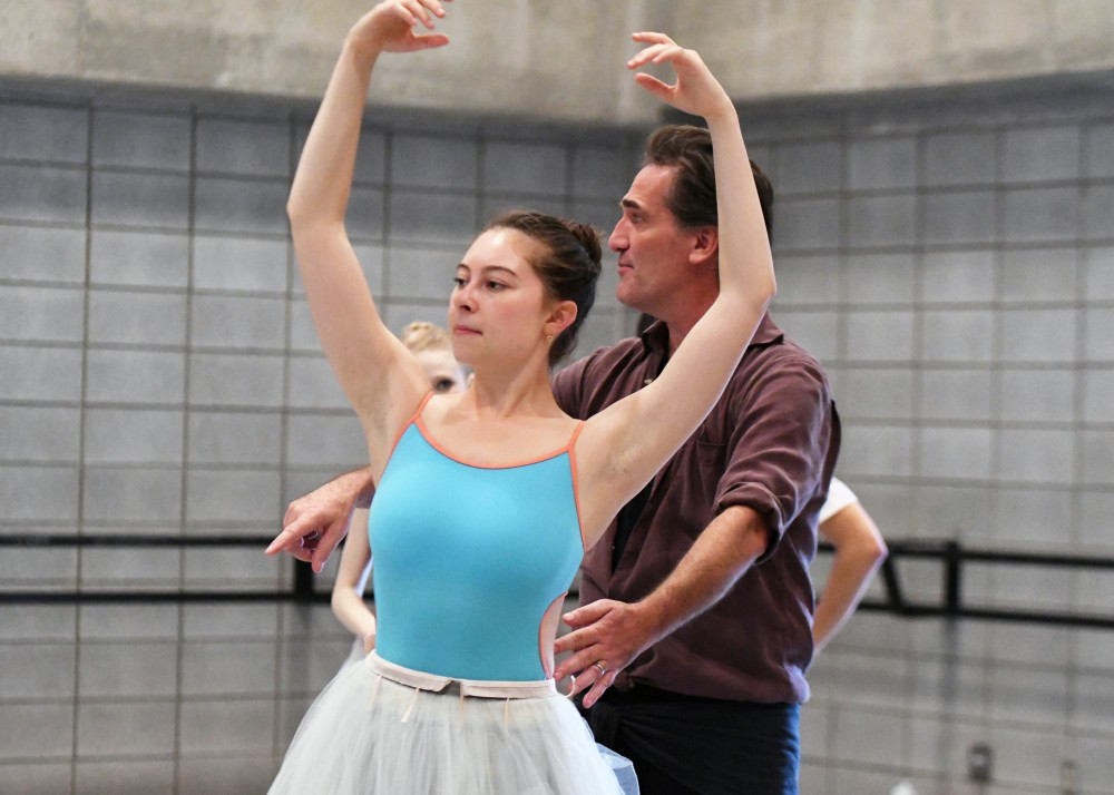 An instructor corrects a ballet student.