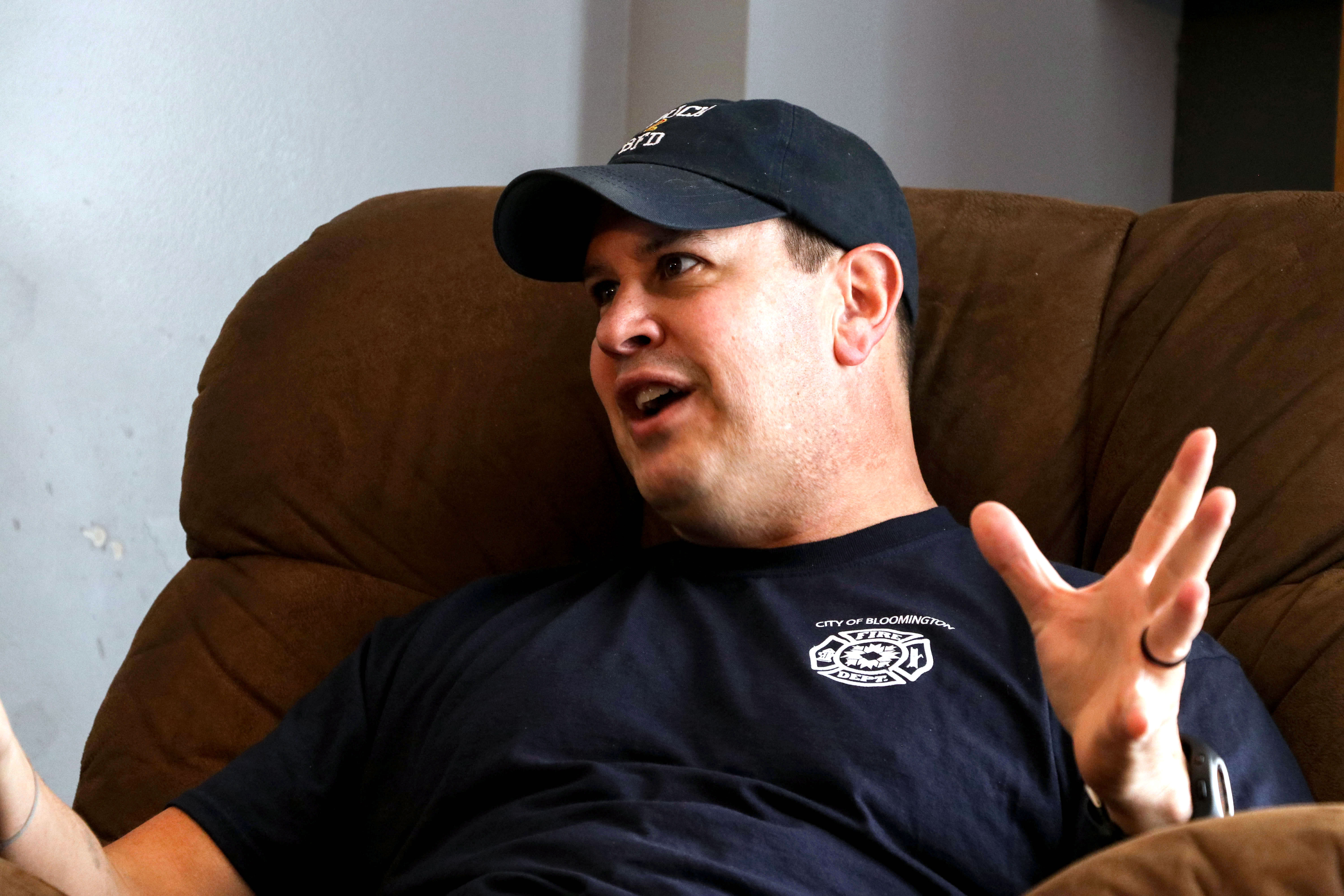 Dan Emerick, wearing a blue cap, makes a hand gesture while sitting in a recliner and looking to his right.