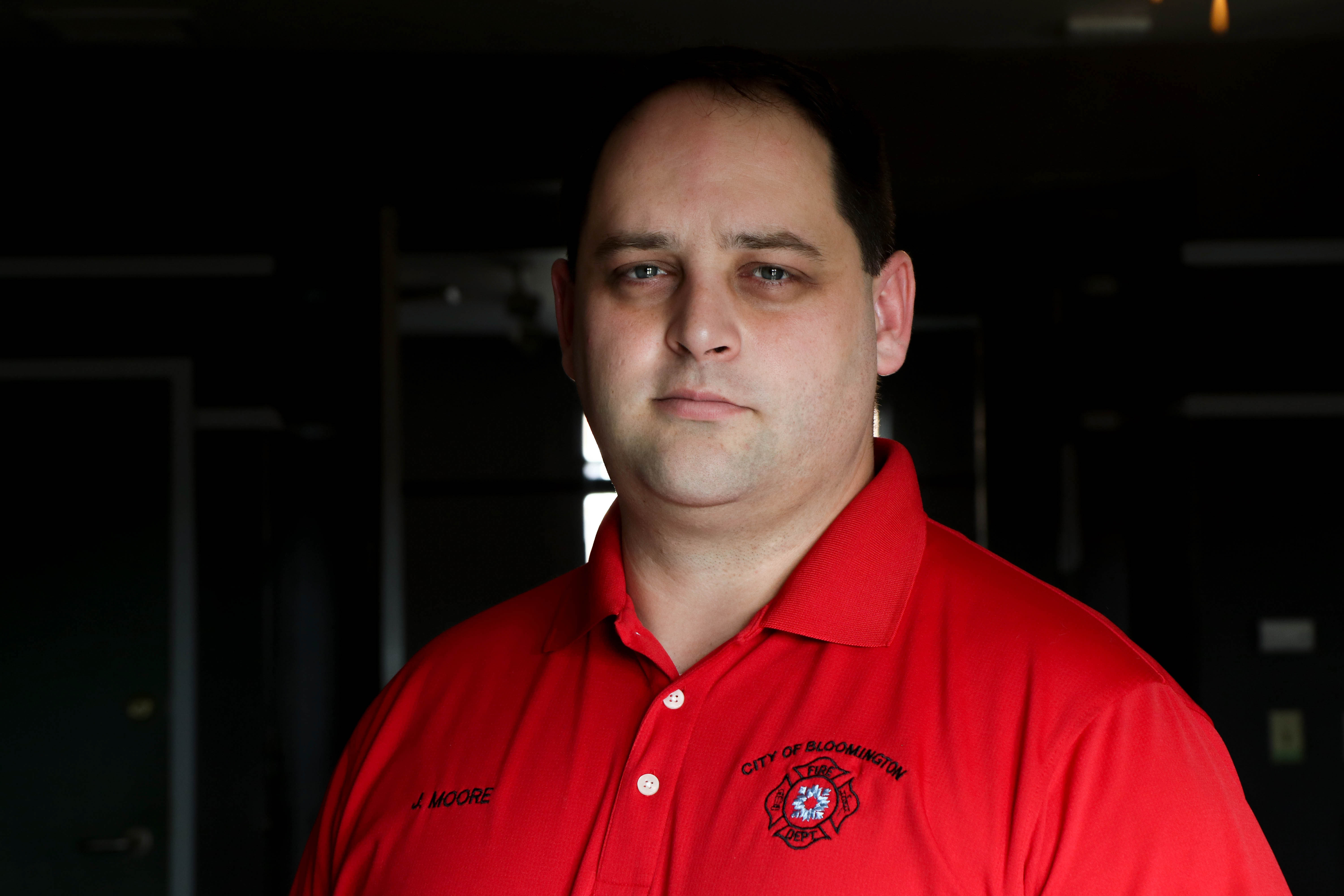 A portrait of Bloomington Fire Chief Jason Moore, who is wearing a red shirt and looking directly into the camera.