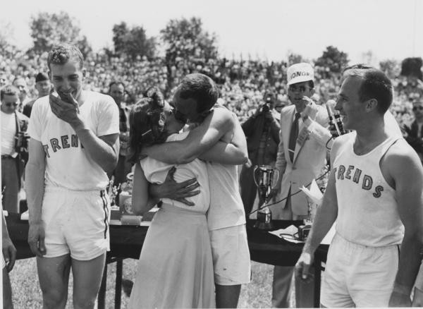 A man and a woman kiss while members of the man's Little 500 team stand nearby. The first team to win the men's Little 500 was the South Hall Buccaneers in 1951.