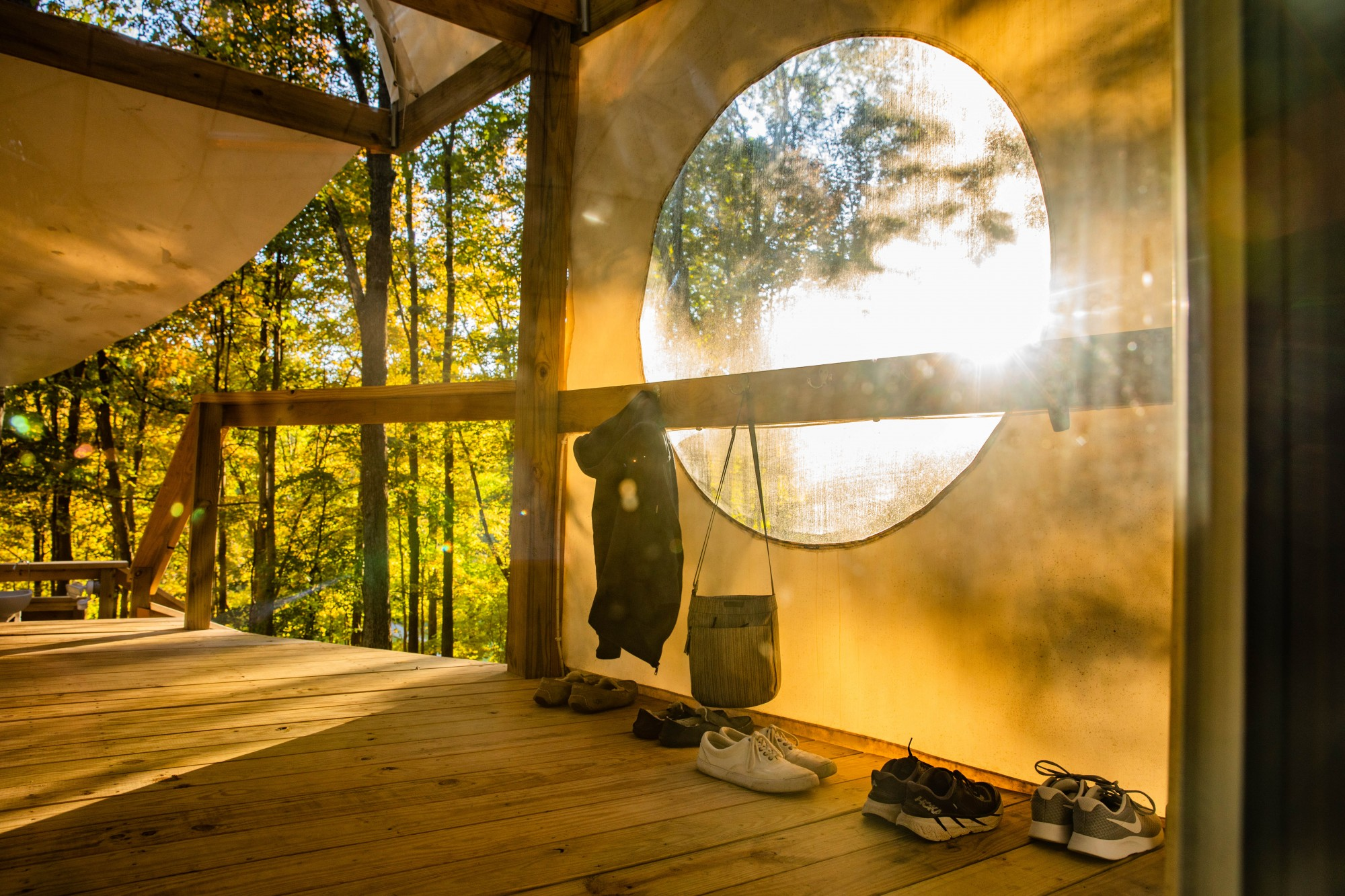 The shoes and personal belongings of students participating in the hot power yoga class at Geode Yoga + Fitness line the exterior of the dome in the dense forests of Chillicothe, Ohio. on Monday, Oct. 5, 2020.