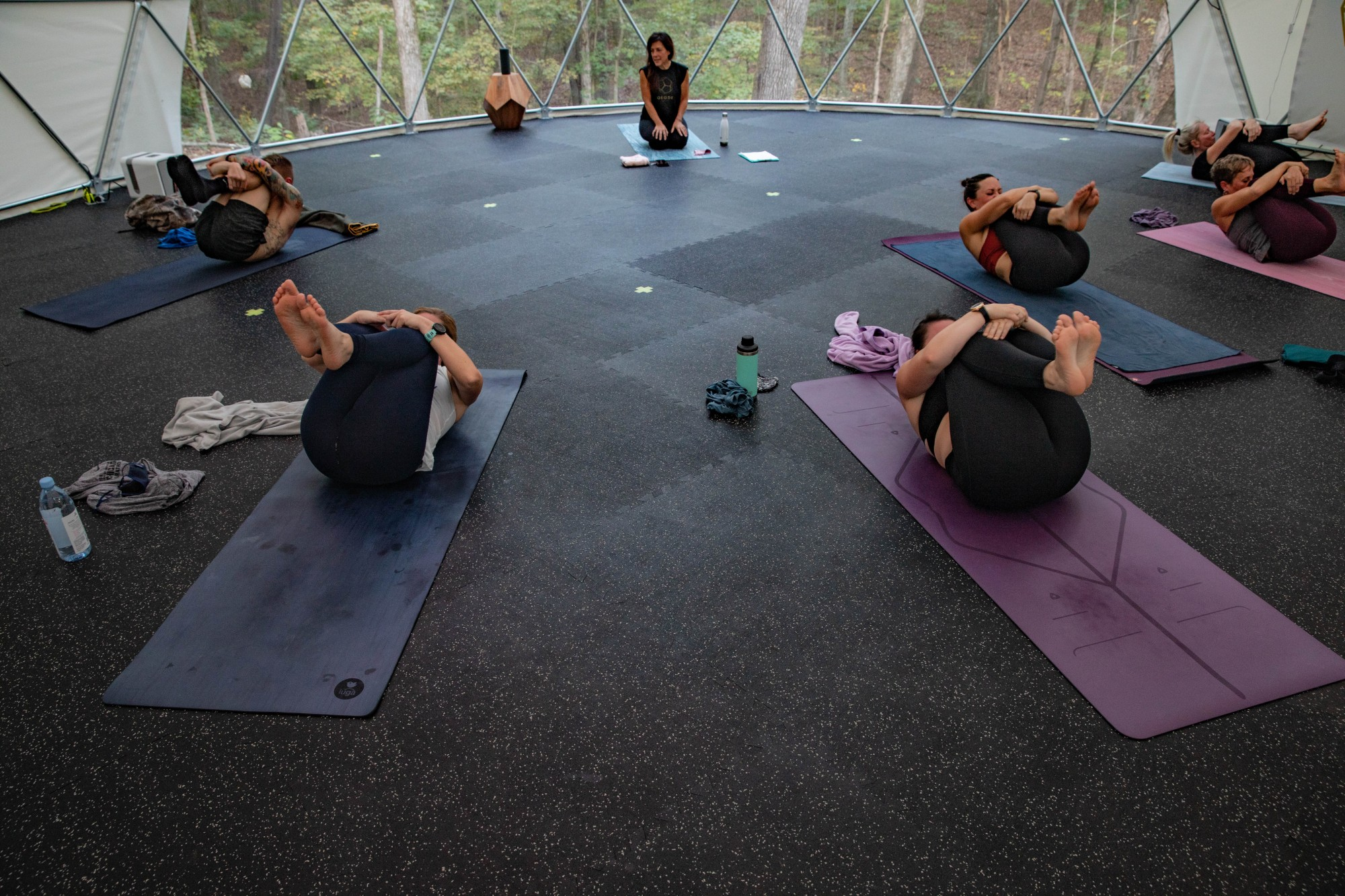 Class participants perform the Happy Baby pose in a hot power yoga session led by Marci Hedderson-Caroll at Geode Yoga + Fitness in Chillicothe, Ohio, on the evening of Monday, Oct. 5, 2020.