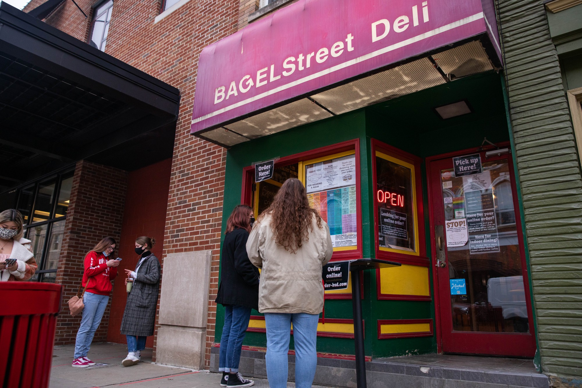 Customers wait for their order outside Bagel Street Deli in uptown Athens, Ohio, on Sunday, February 14, 2021.