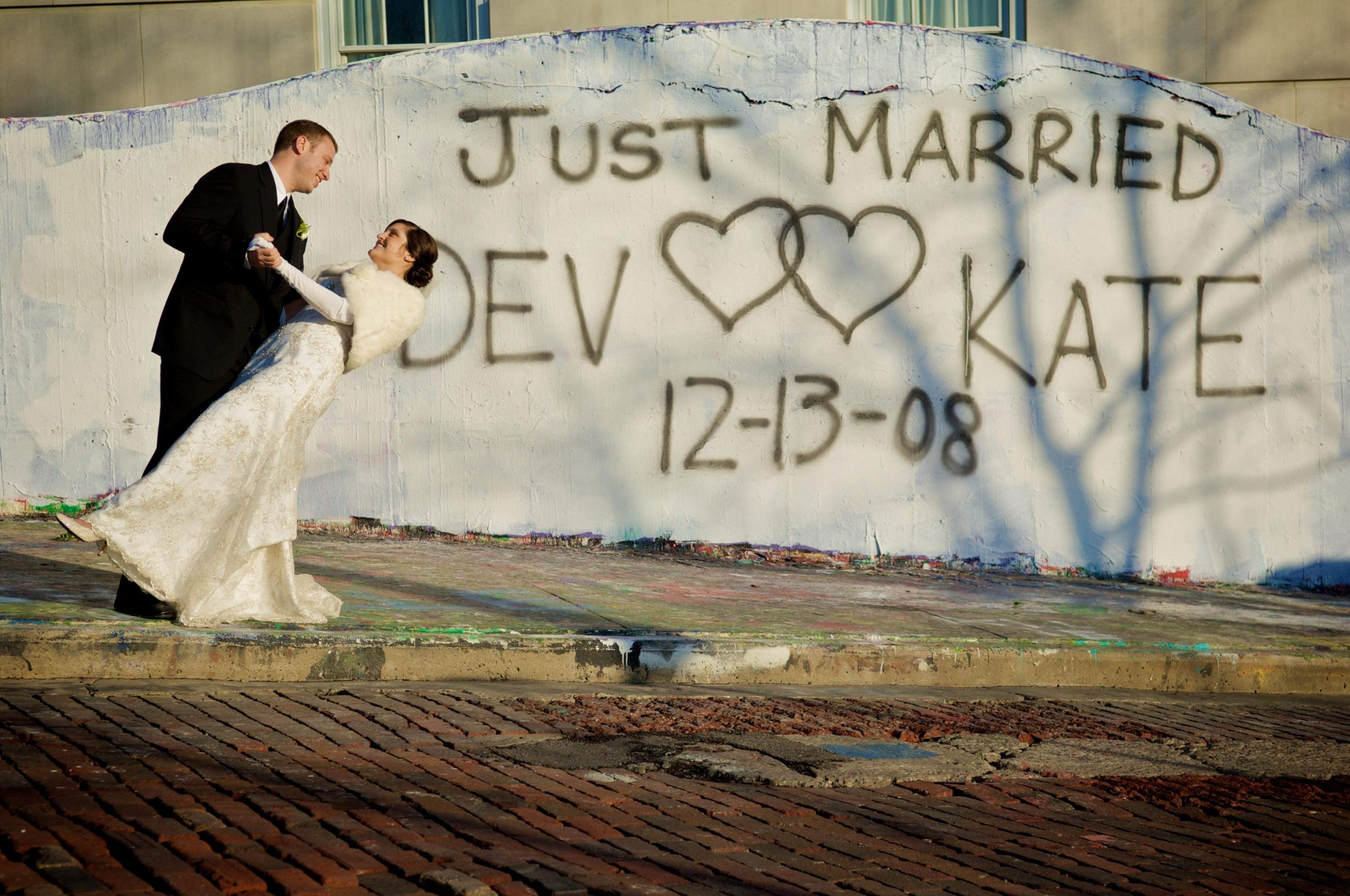 Katie and Devan Cropp pose in front of the graffiti walls after their wedding.