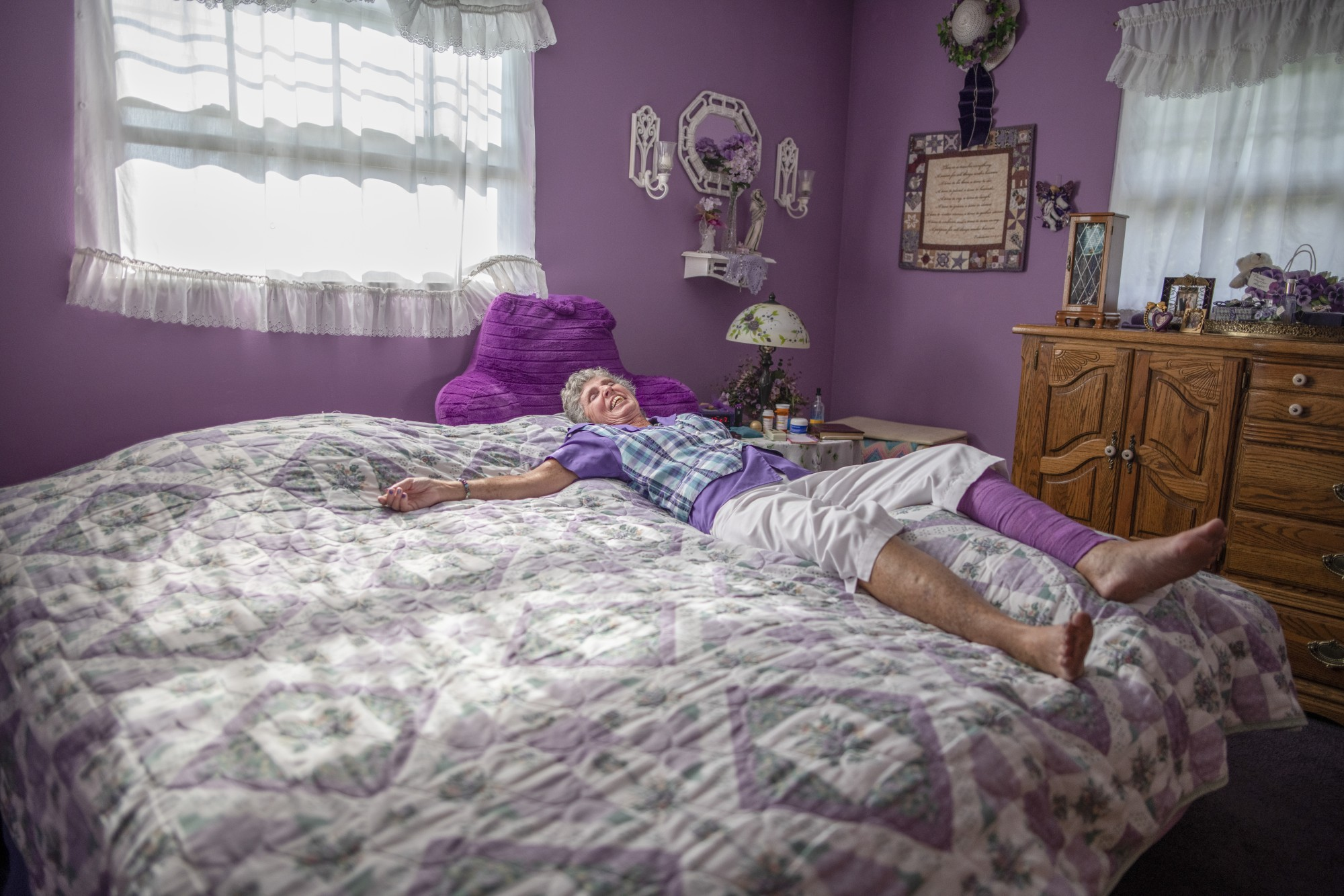 Cheryl Brockman, 71, of Bellbrook, Ohio, lays in her 'purple bedroom,' on the morning of Sept. 8, 2020.  Cheryl loves the color purple and collects all things purple. 'My husband tells me if I bring home one more thing that's purple, I'm going to have to take it right back.'
