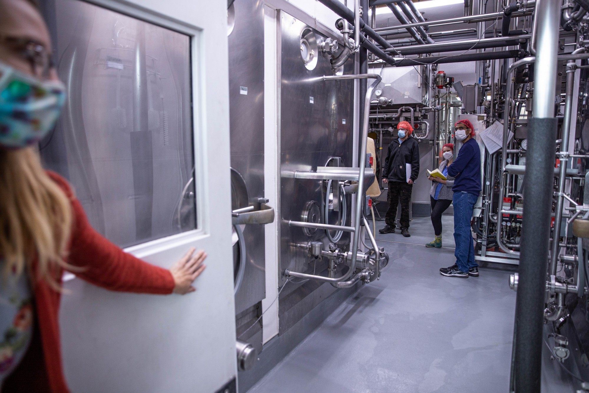 A team meeting is held inside a processing room inside the Snowville Creamery plant in Pomeroy, Ohio, on Monday, Nov. 16, 2020.