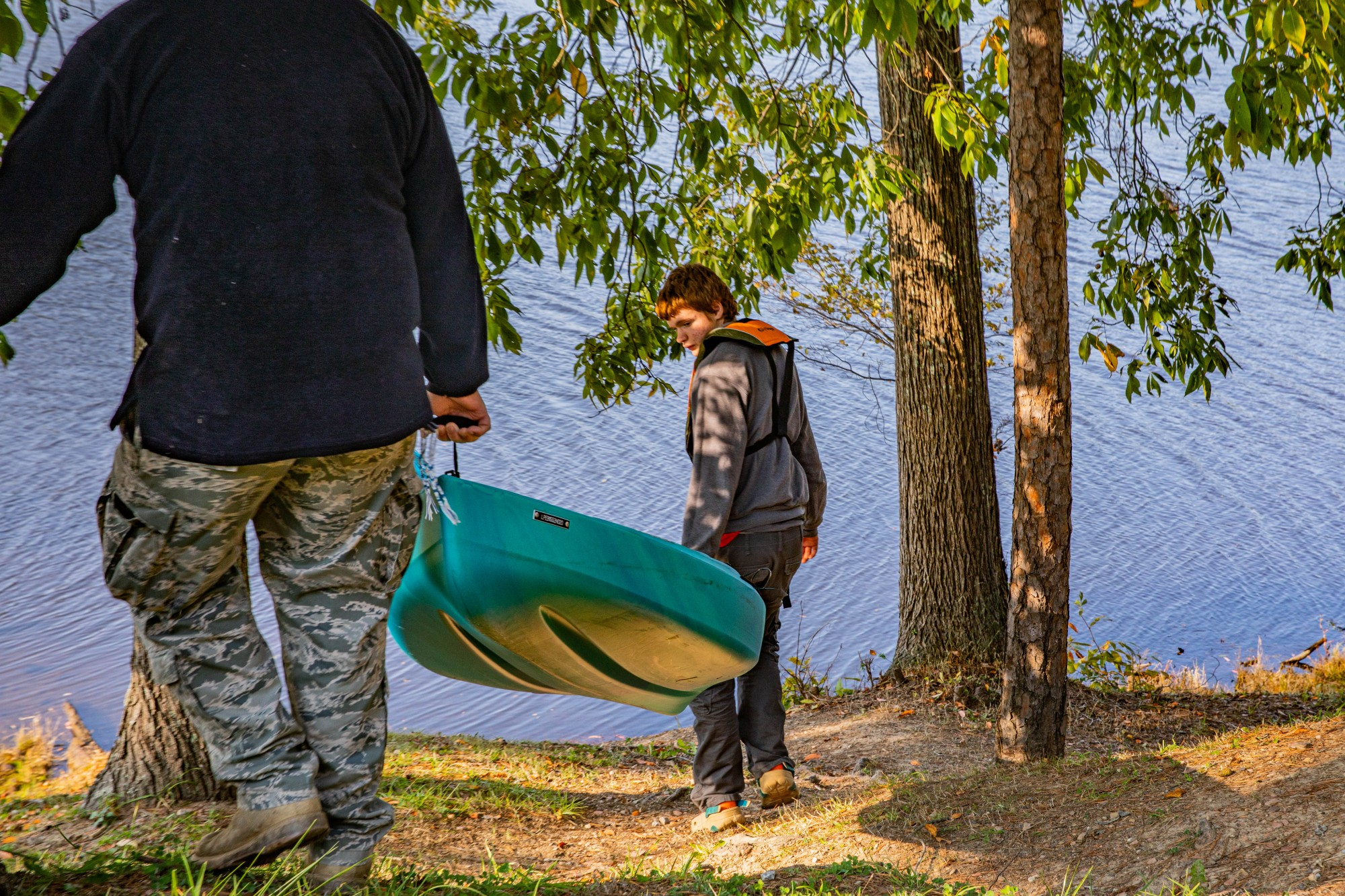 """Stacey Scott assists his son, Micah, with carrying his brand-new kayak from his birthday into thd banks of Lake Hope in McArthur, Ohio, on Tuesday, Oct. 6, 2020. """"We've been out here for a couple weeks,"""" Stacey Scott says, """"When I was stationed out west, the one thing I missed the most was the change in color here around this time."""""""