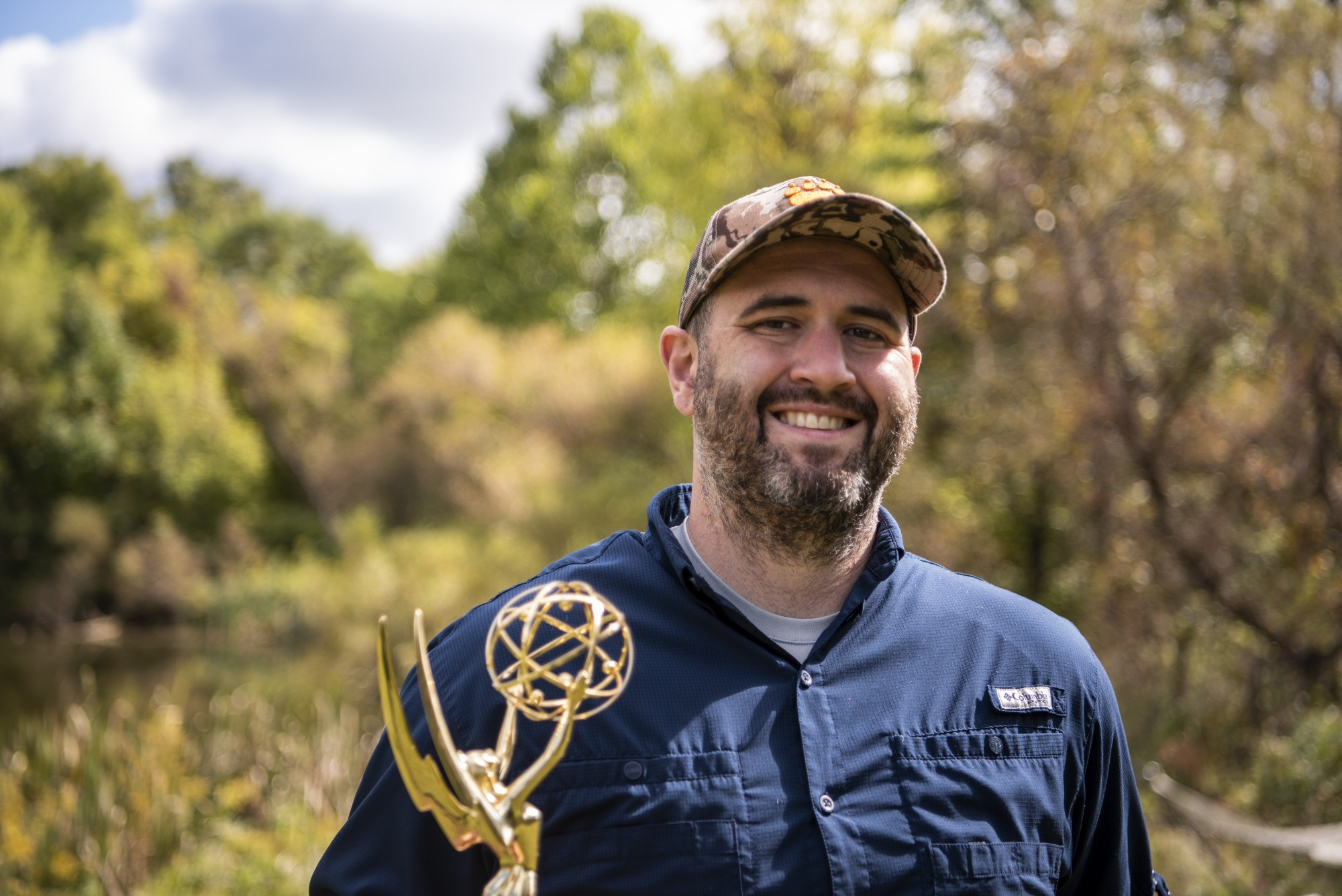 Ten-time Emmy winning filmmaker, Evan Shaw, poses for a portrait in his backyard in Athens, Ohio, with his signature camouflage hat and one of his Emmys.
