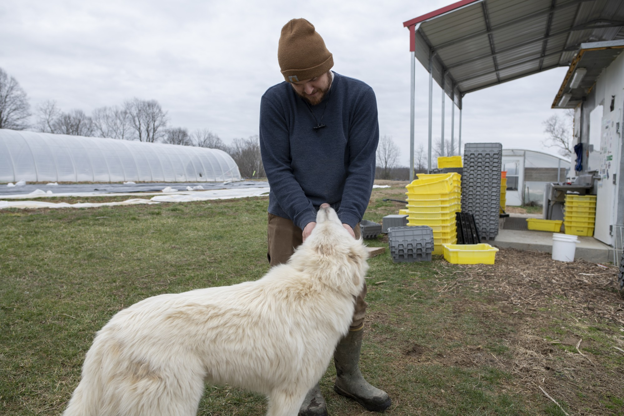 Adam Blaney plays with his dog, on his farm in Albany, Ohio, on March 2, 2020.