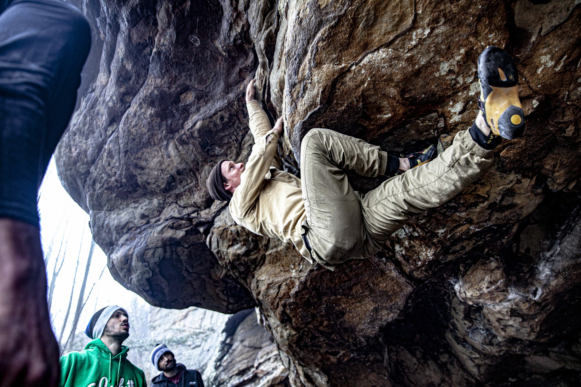 Aaron Warrens, left, Justin Mamaril, middle, and Jarrod Mamaril, right, watch and support Jason Voss as he climbs a boulder problem at Johnny Chimpo in New River Gorge, West Virginia on Saturday, Feb. 28, 2021. Voss was the only one able to finish the boulder problem on that rainy day, even after more than five hours of attmepts.
