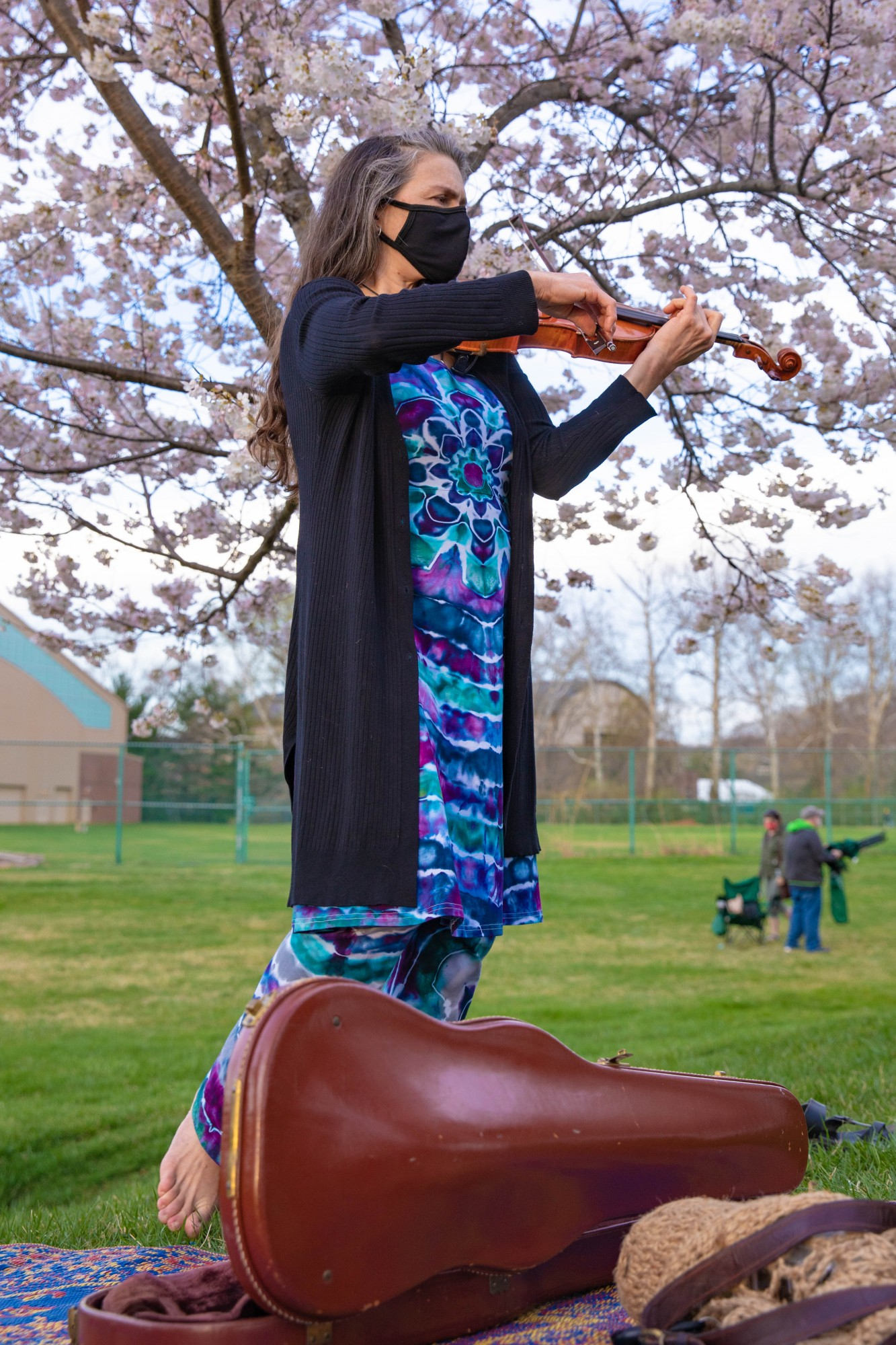 Karen Richards plays her violin between the rows of cherry blossom trees along the Hocking River as the sun begins to set on Tuesday, March 30, 2021.