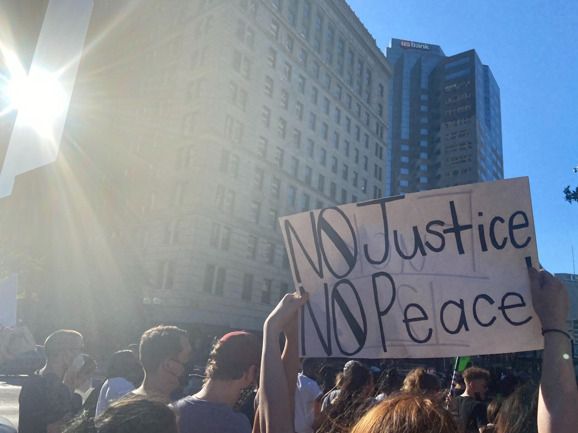 Protestors hold up a 'No Justice, No Peace' sign while walking.