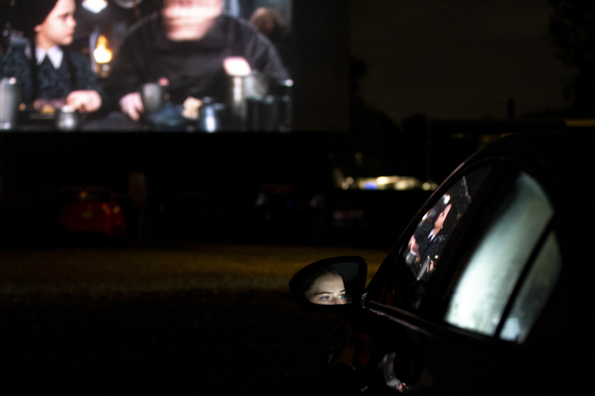Mara Brooks and Olivia Neff do their online homework as they watch 'Hocus Pocus' and the live action 'The Addams Family' at the Starlite drive-in of Amelia, OH. Brooks and Neff are big fans of the drive-in and 'Hocus Pocus' so they felt they had to buy tickets for the screening the weekend of Oct. 4, 2020. (Jesse Jarrold-Grapes. For The Post)