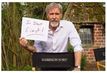 "Harrison Ford holding a sign with the statement ""I shot first!"""