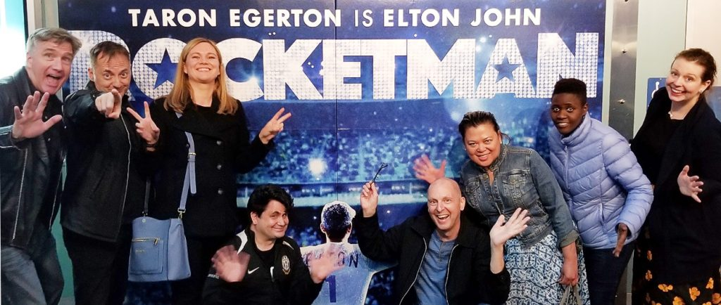 the STR Gang and winners of the Elton John biopic Rocketman ticket contest infront of the movie poster