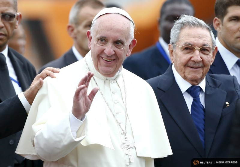 Pope Francis waves as he arrives, accompanied by Cuba's President Raul Castro, at the Havana airport